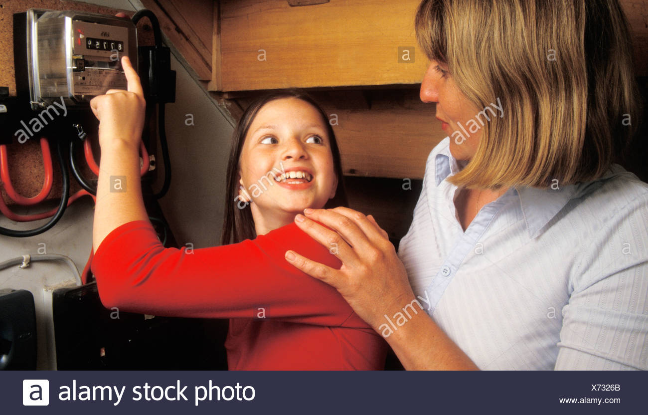 woman and child under stairs reading electricity meter - Stock Image