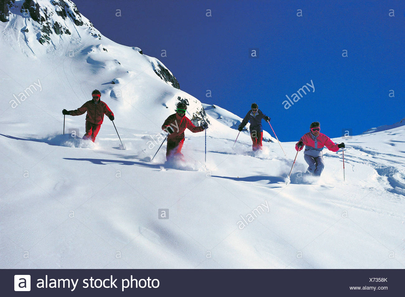 Group of four skiers in white powder snow. - Stock Image