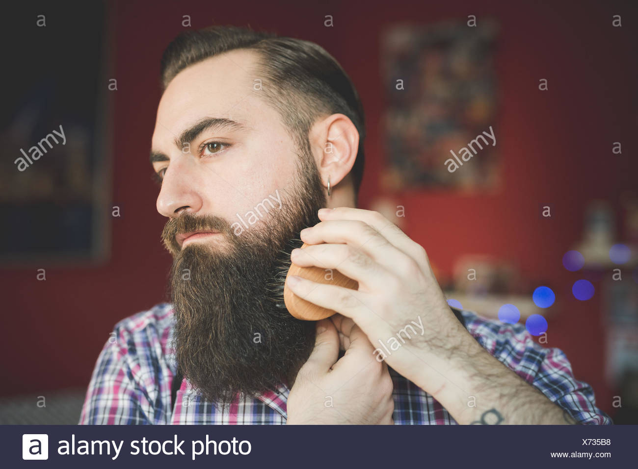 Young bearded man brushing his beard - Stock Image