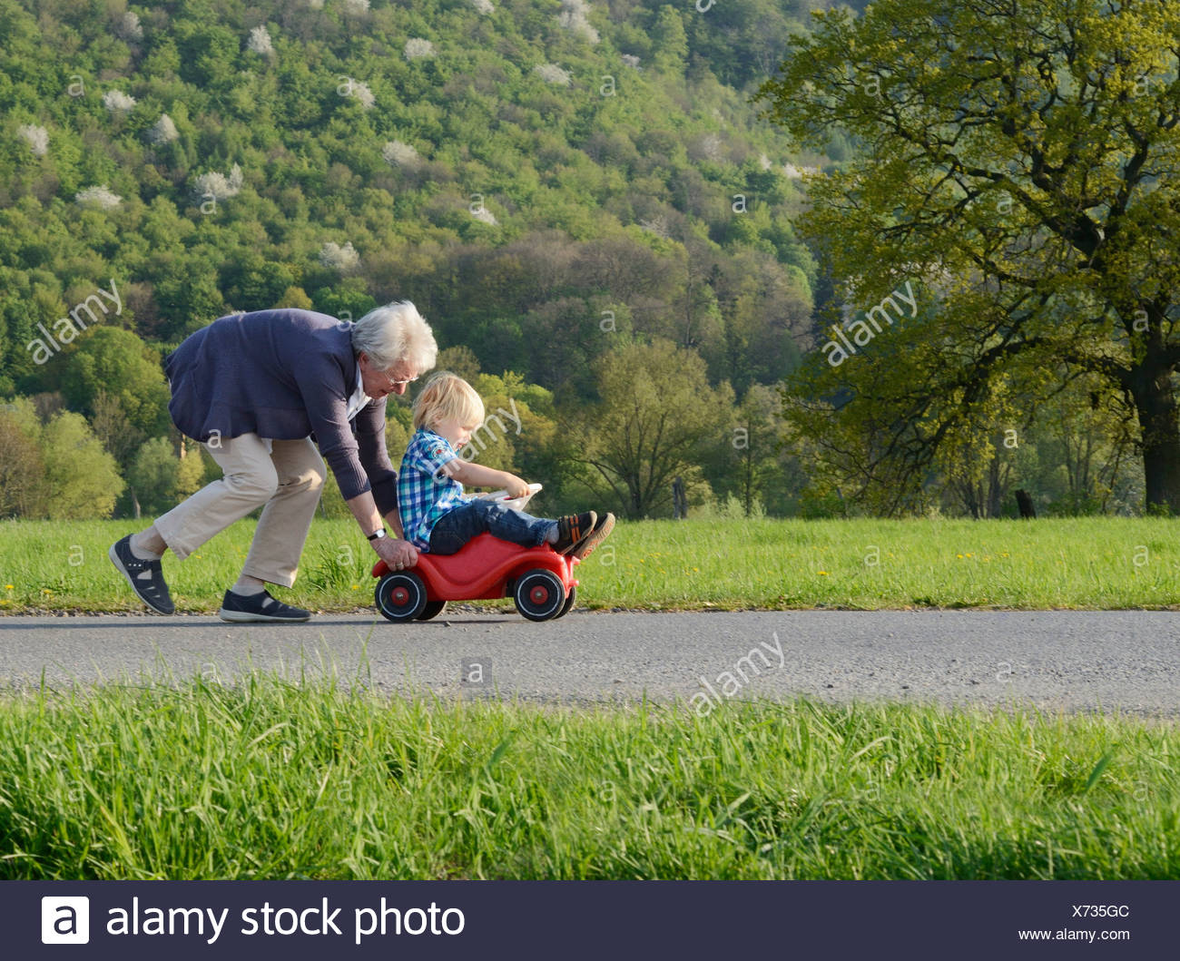 Grandmother pushing boy on go kart - Stock Image