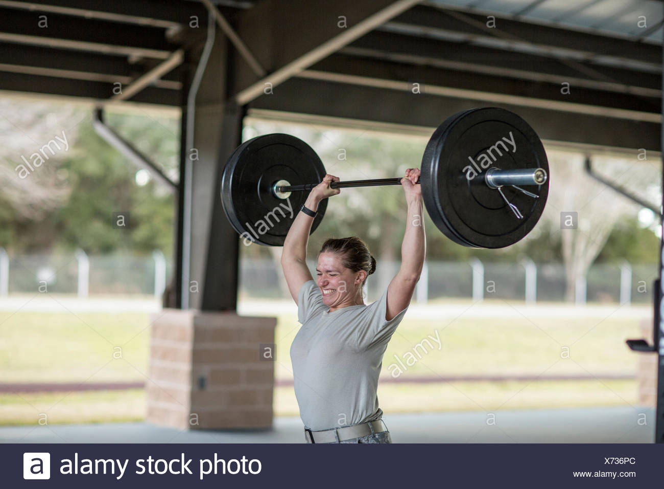 Determined female soldier lifting barbell at military air force base - Stock Image