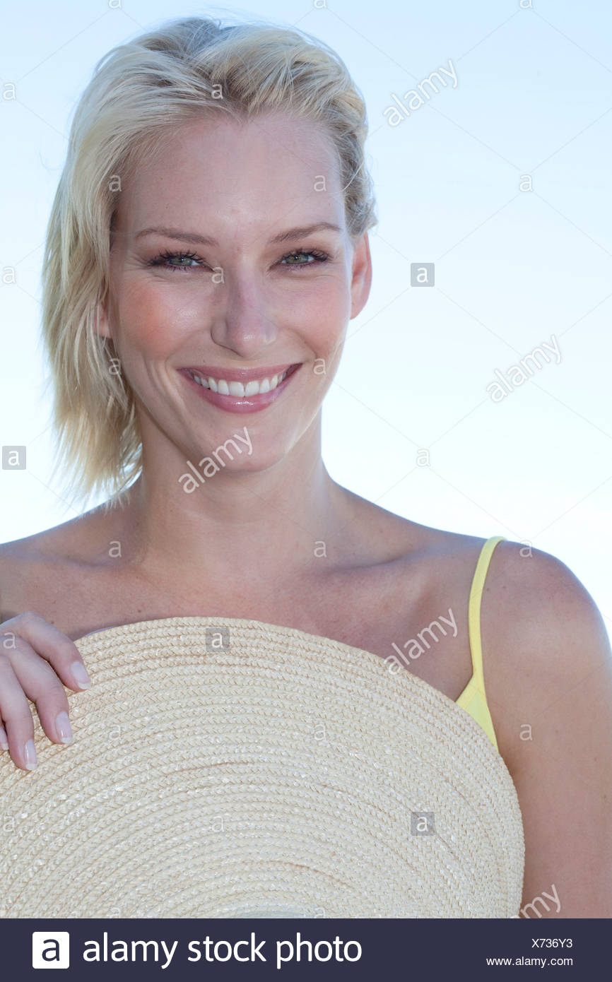 Female with wide-brimmed straw hat - Stock Image
