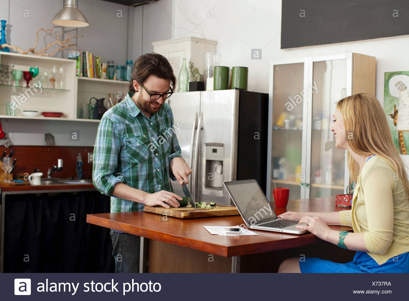 Woman on laptop computer, man chopping vegetables - Stock Image