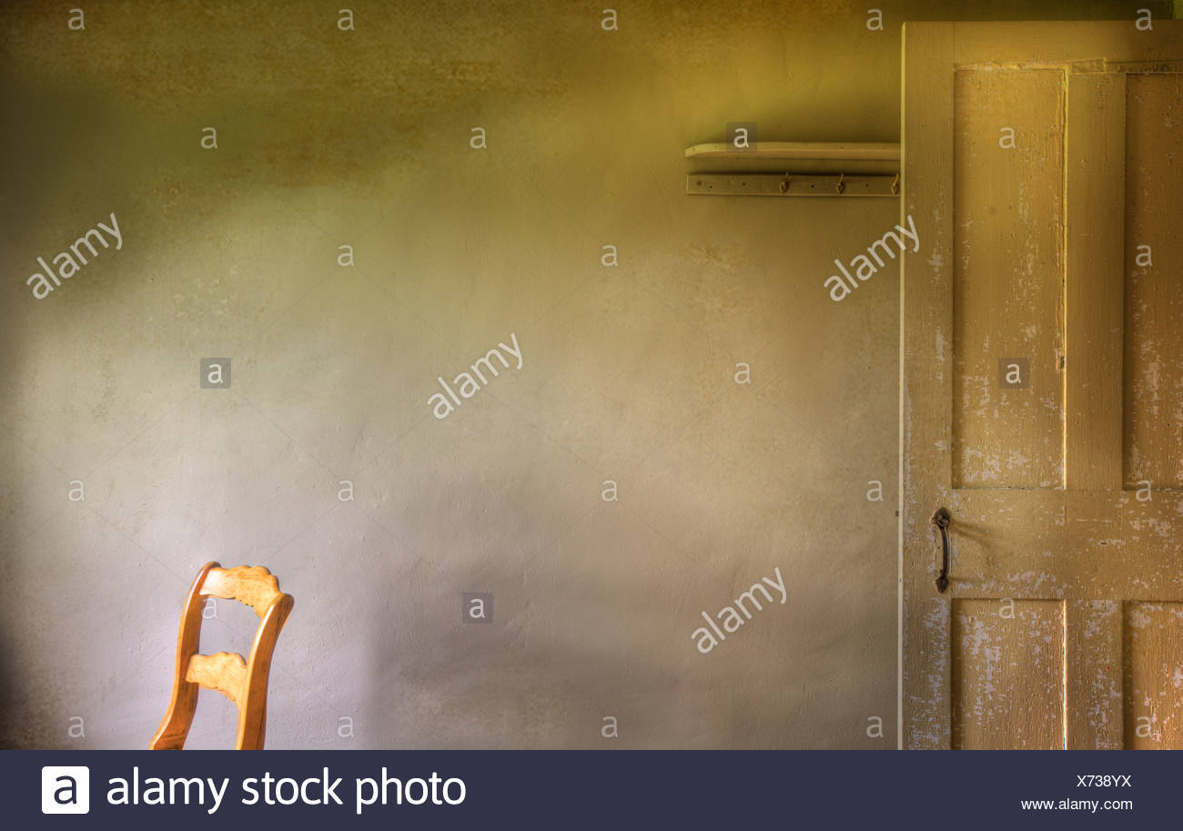 Chair with window light and door in the shadows. - Stock Image