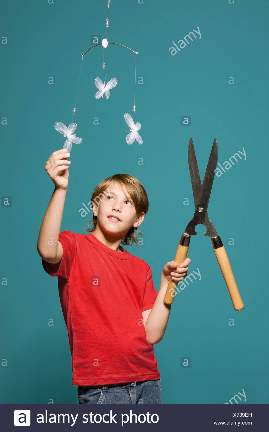 Boy with hedge clippers looking up at butterfly mobile - Stock Image