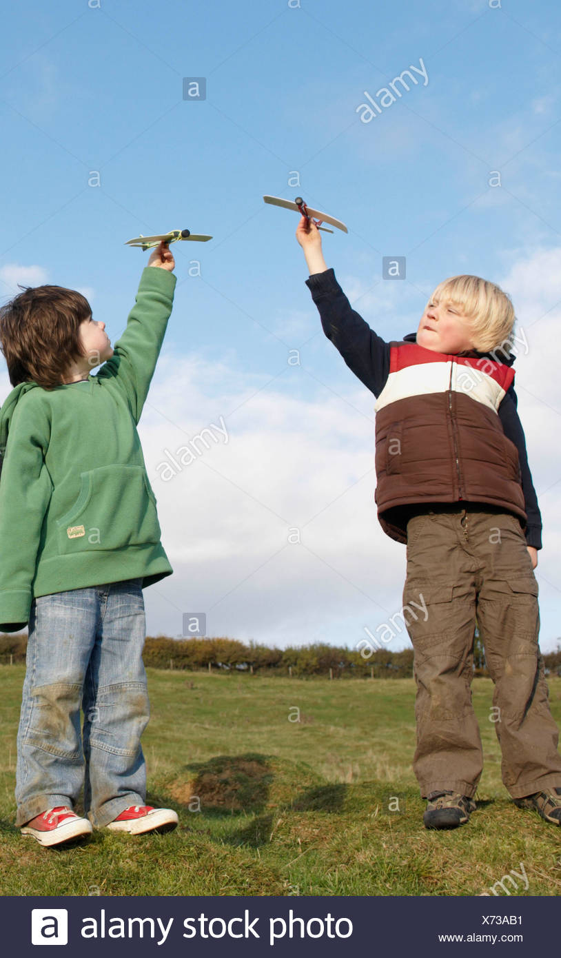 Boys with toy planes in field - Stock Image