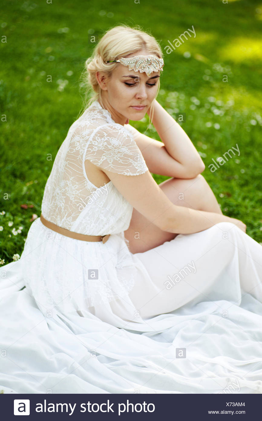 Woman sits in the white dress on meadow - Stock Image