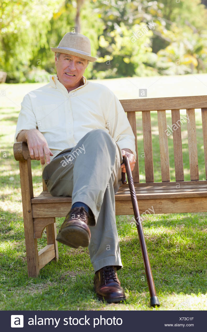 Man smiling while siting on a bench as he hold a cane - Stock Image