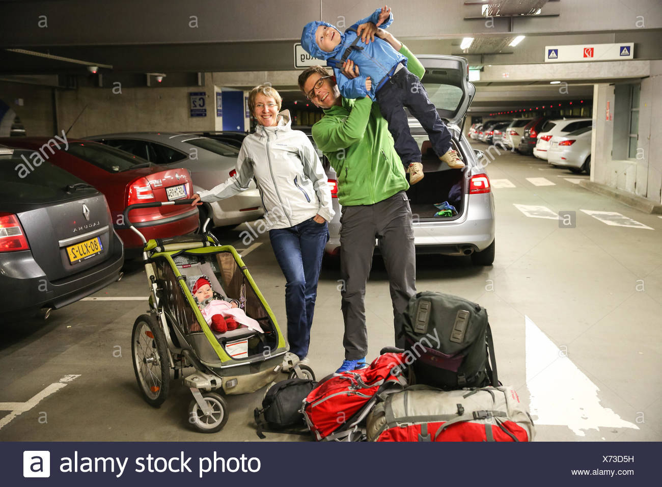 Young family with children, departure at airport, car parking area, baby, small boy, luggage, stroller, backpack, parental leave - Stock Image