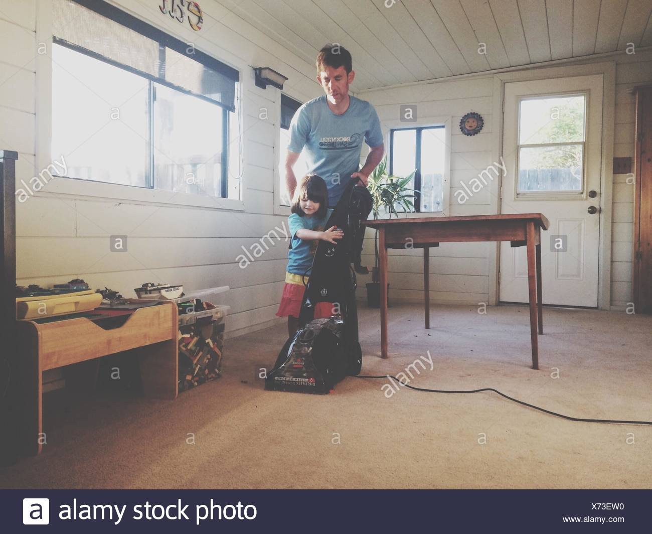 Father And Girl With Vacuum Cleaner At Home - Stock Image
