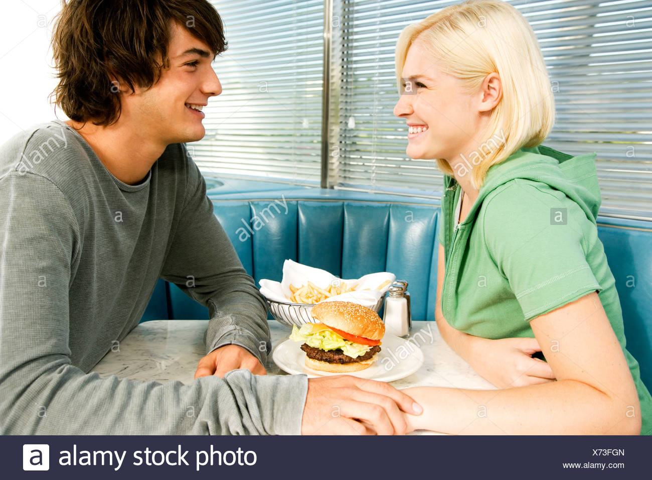 teenage couple in a diner smiling and looking into each other's eyes over a hamburger - Stock Image
