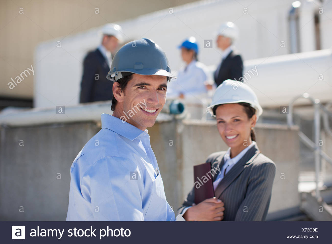 Business people in hard-hats outdoors - Stock Image