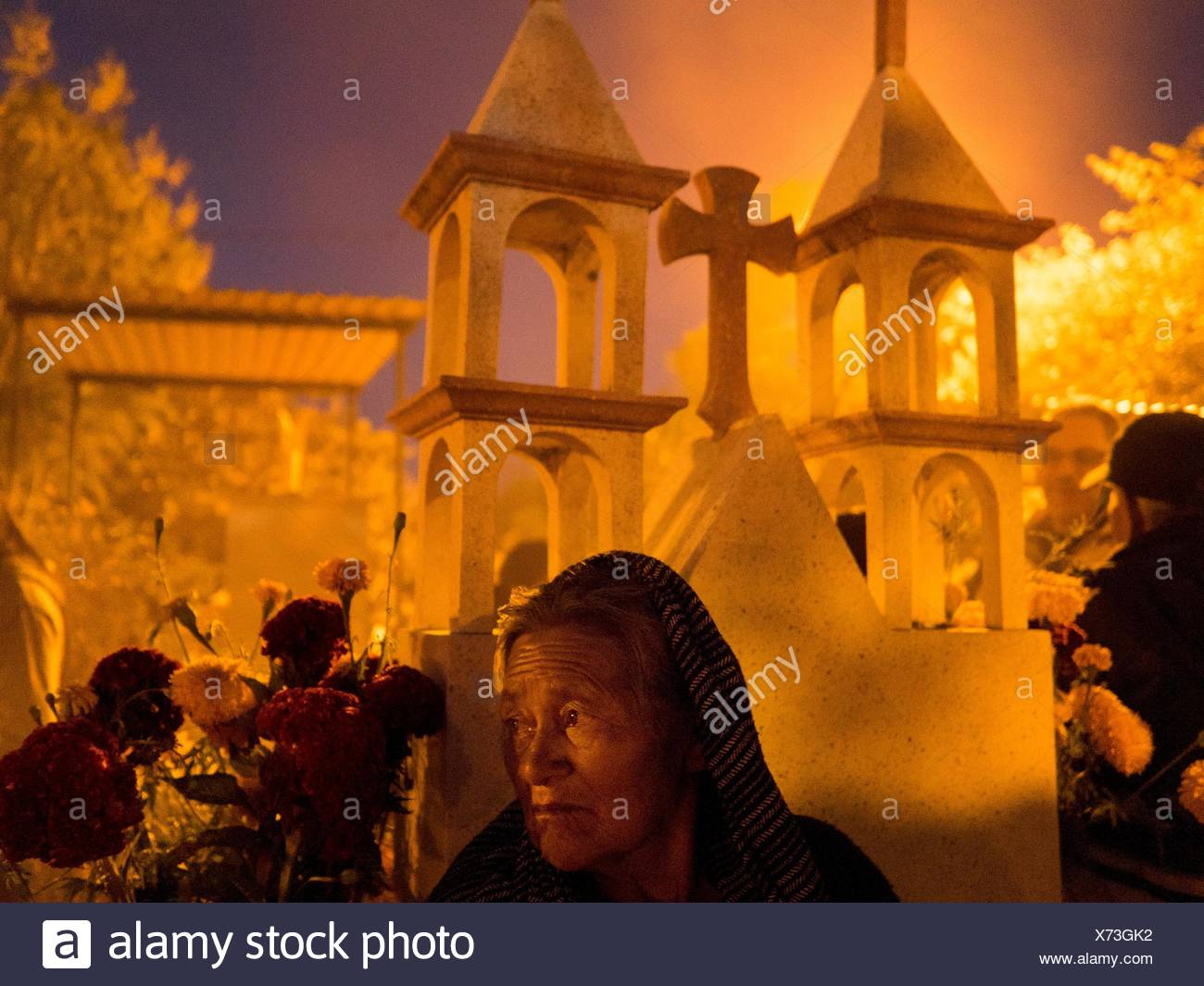 People tend graves in a cemetery for the Day of the Dead celebrations. - Stock Image