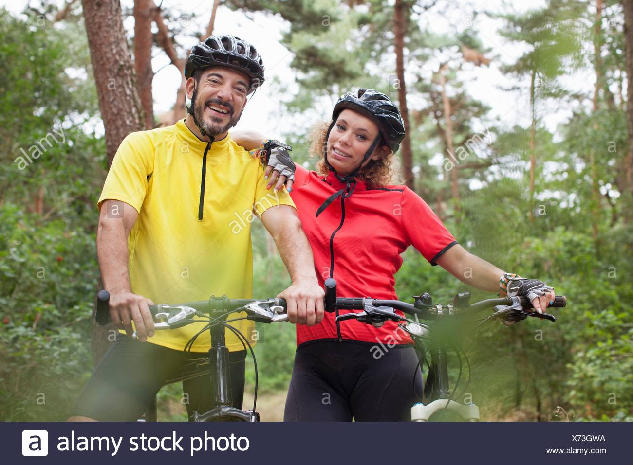Portrait   happy mountain biking couple in forest - Stock Image