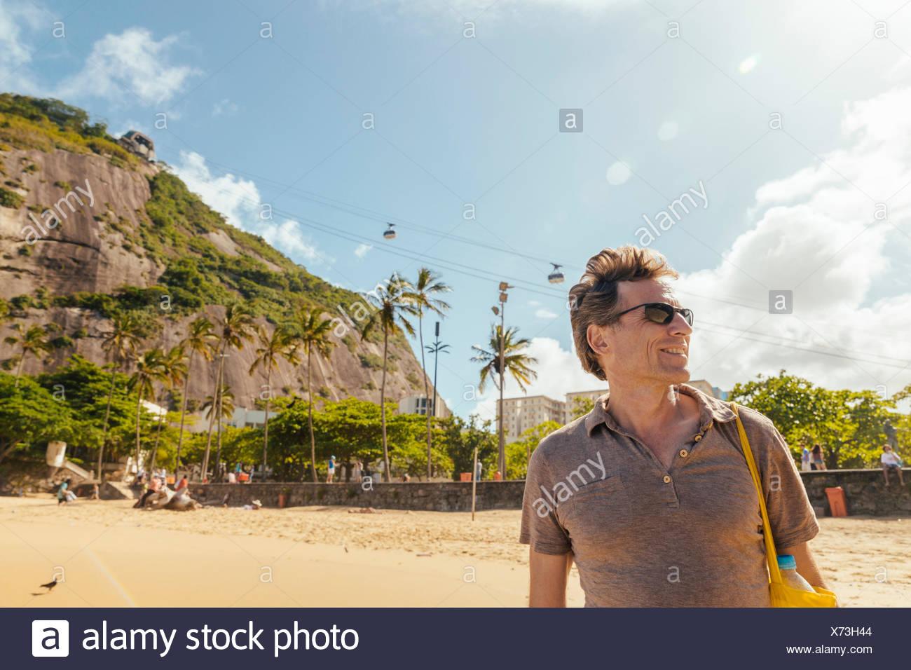 Brazil Morro da Urca behind a male tourist on Praia Vermelha in Rio de Janeiro Stock Photo