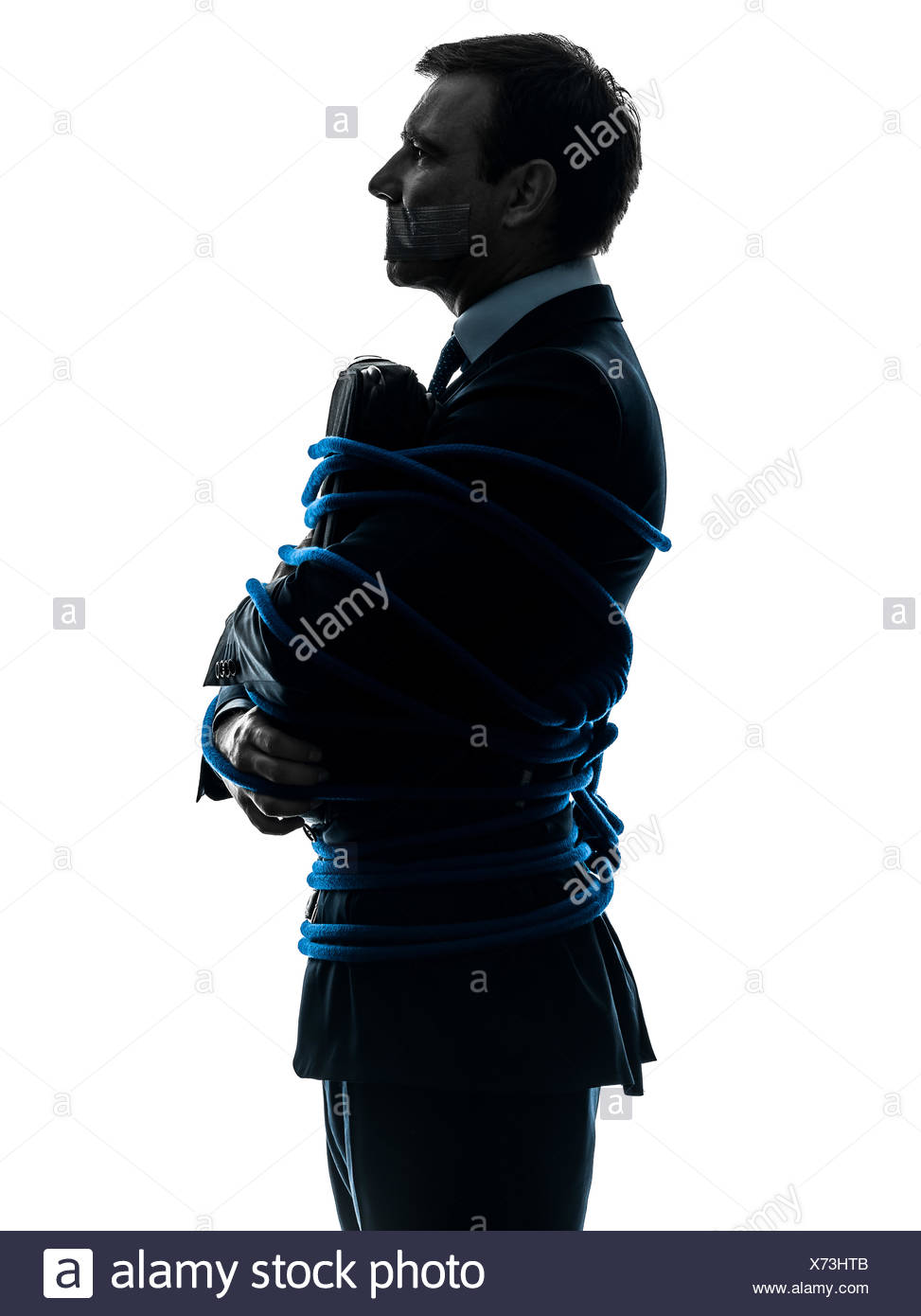 one caucasian business man tied up prisoner  in silhouette studio isolated on white background Stock Photo