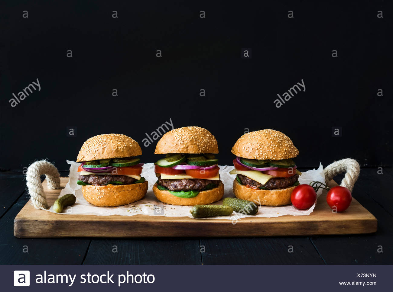 Fresh homemade burgers on wooden serving board over black  background. - Stock Image