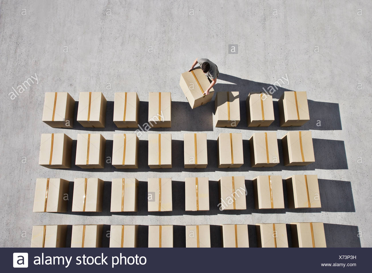 Man placing box into line - Stock Image