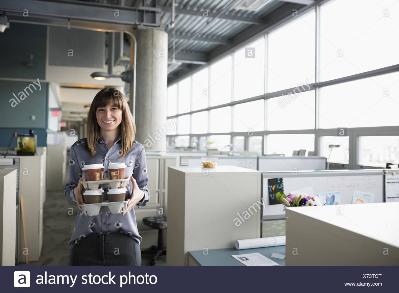 Portrait smiling,generous businesswoman carrying trays of coffee in office - Stock Image