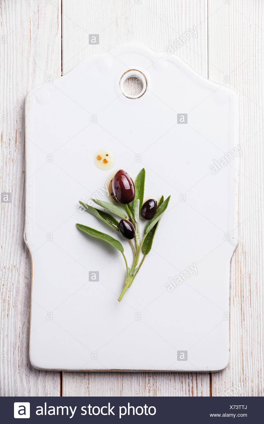 Olives with sage leaves on white background - Stock Image