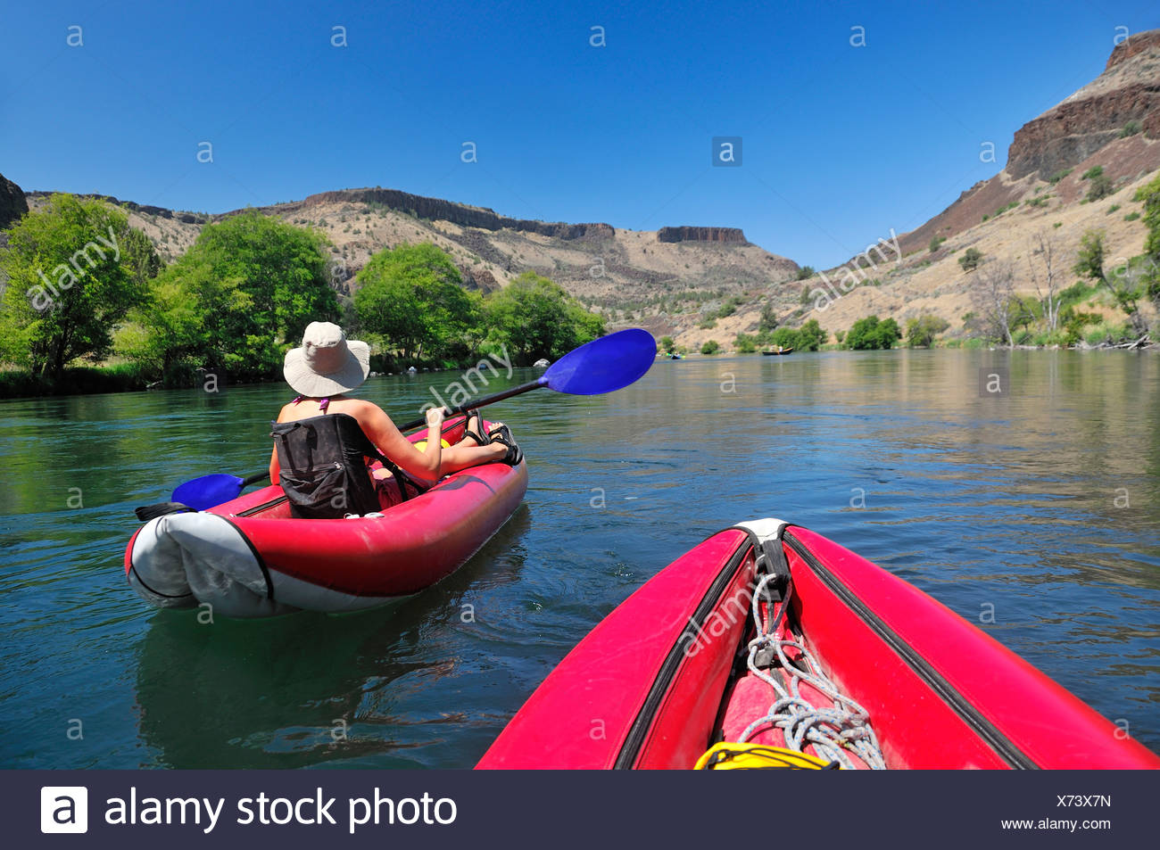 A woman in an inflatable raft on the Deschutes River in Oregon. - Stock Image