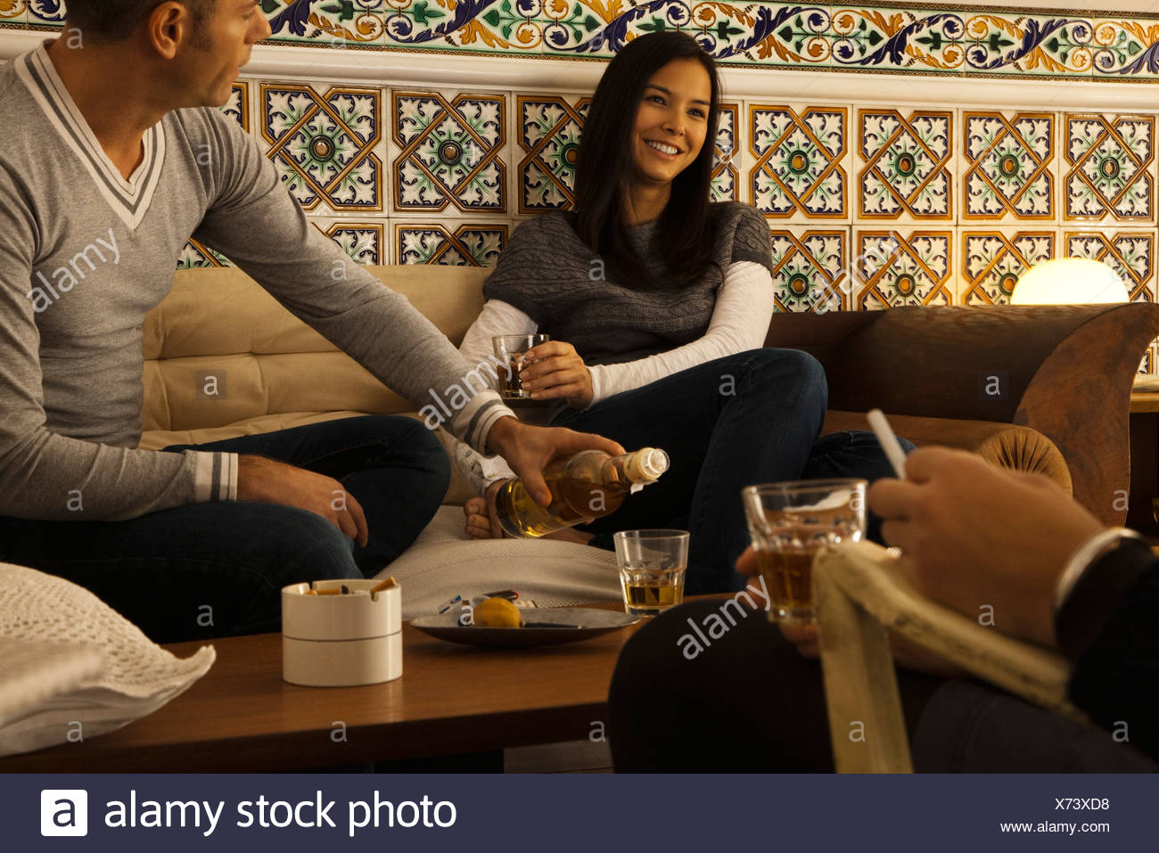 Friends hanging out together in living room - Stock Image