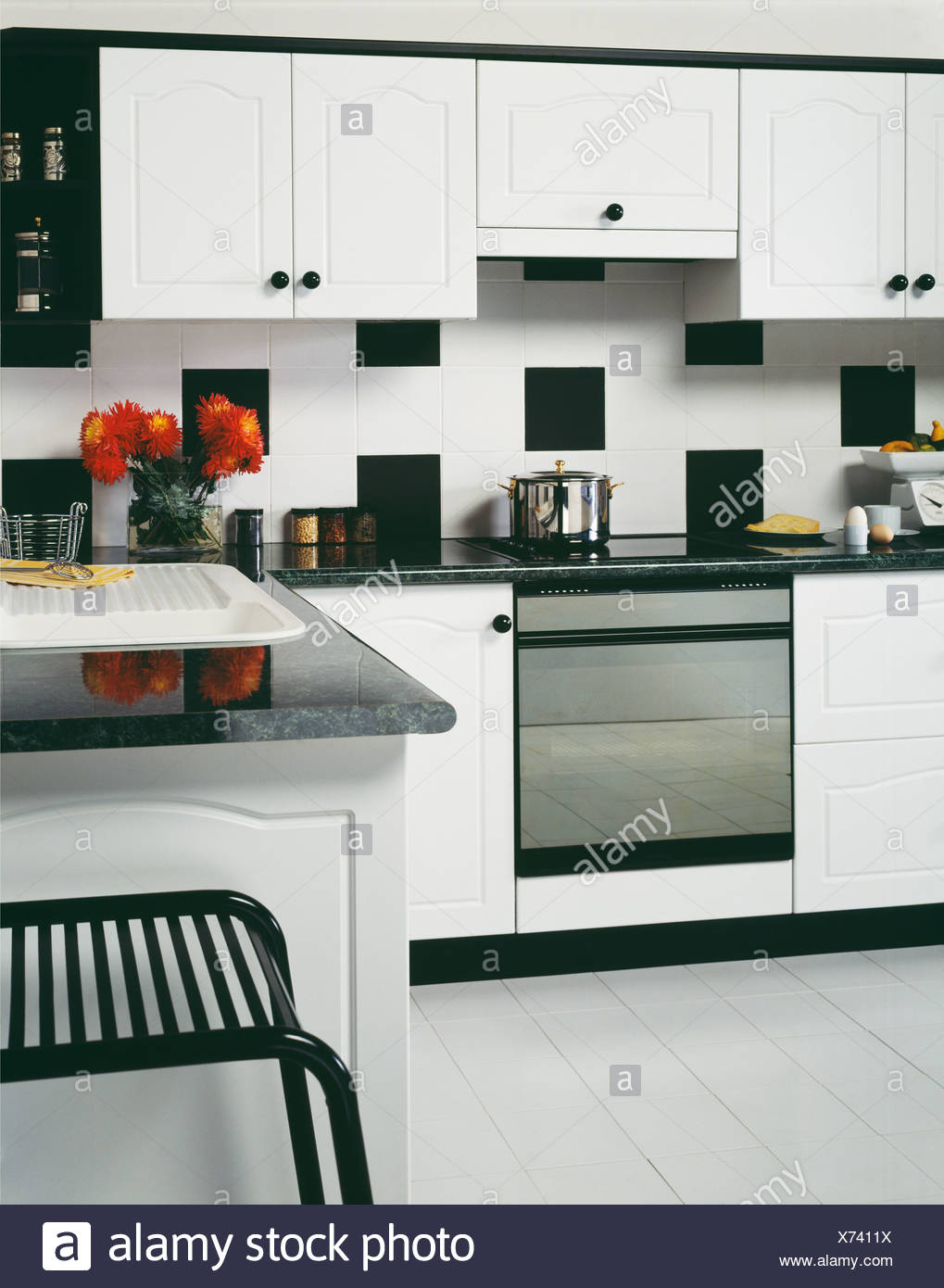 Stainless Steel Oven In Unit Below Wall With Black And White Tiles In Monochromatic Kitchen With Painted White Wooden Flooring Stock Photo Alamy