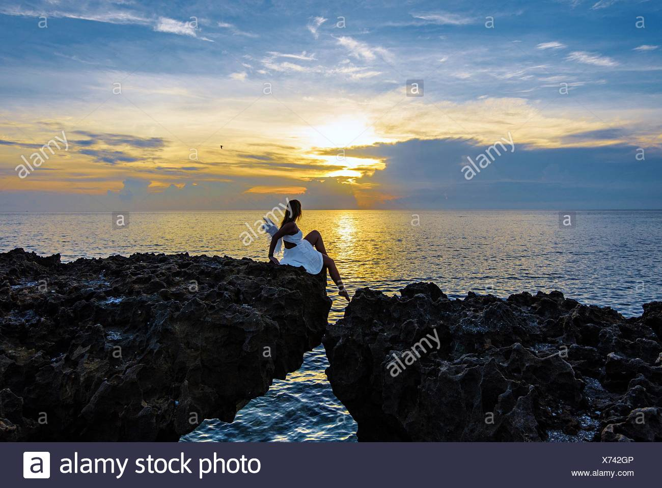 Woman Sitting On Cliff Over Sea Against Sky During Sunset - Stock Image