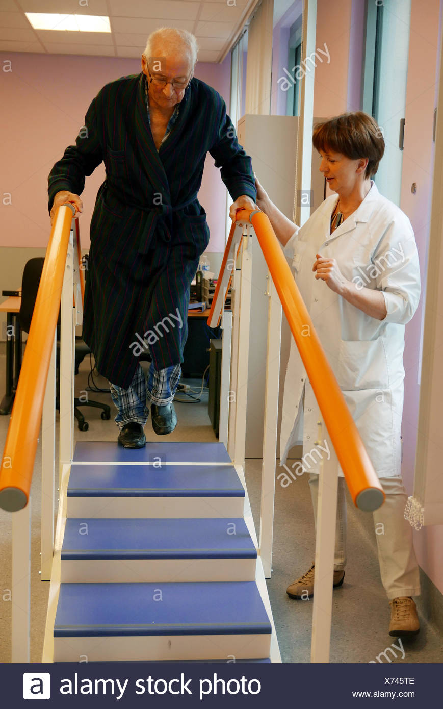 Physical Therapist Assisting Senior Man In Climbing Steps At Nursing Home - Stock Image