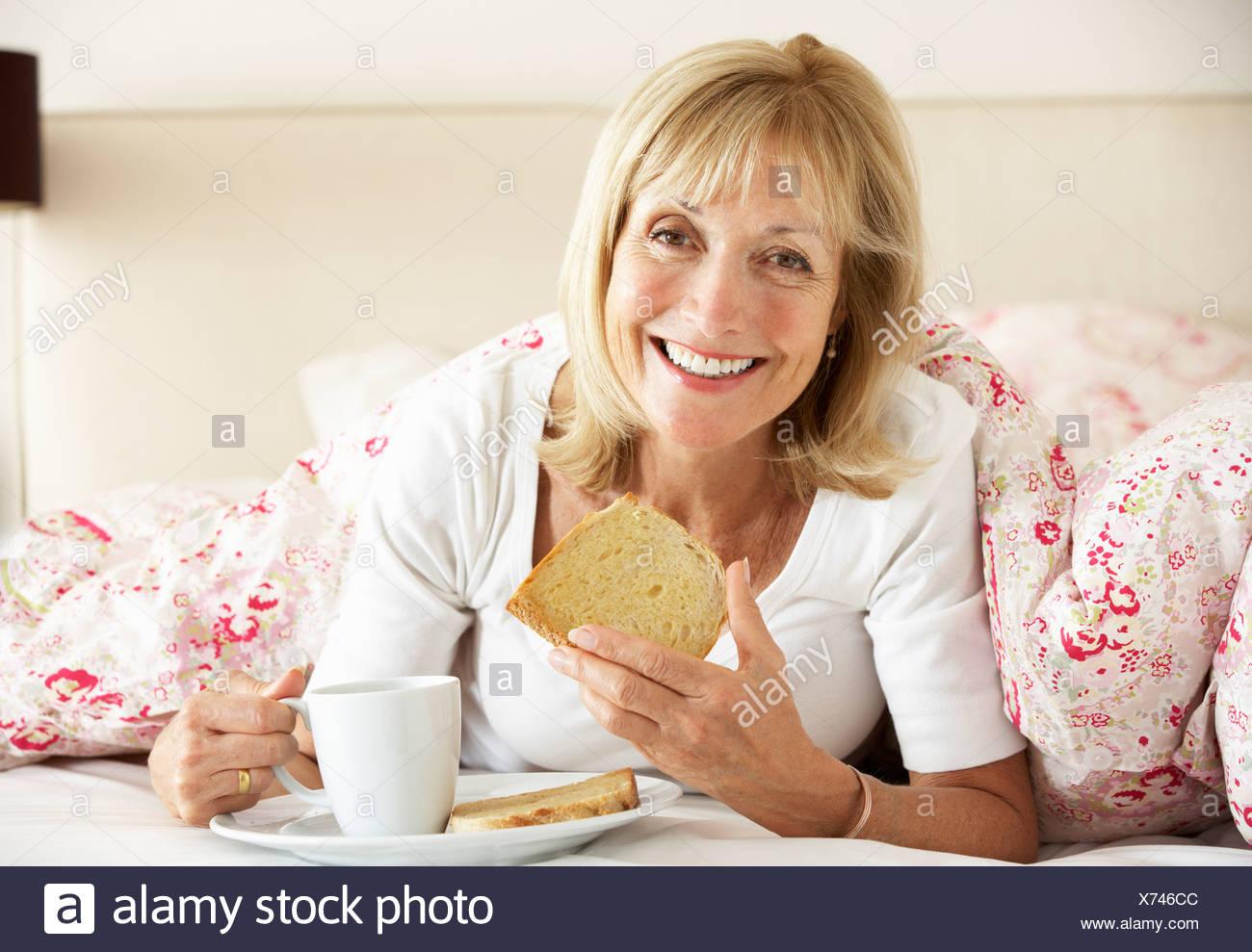 Senior Woman Snuggled Under Duvet Eating Breakfast - Stock Image