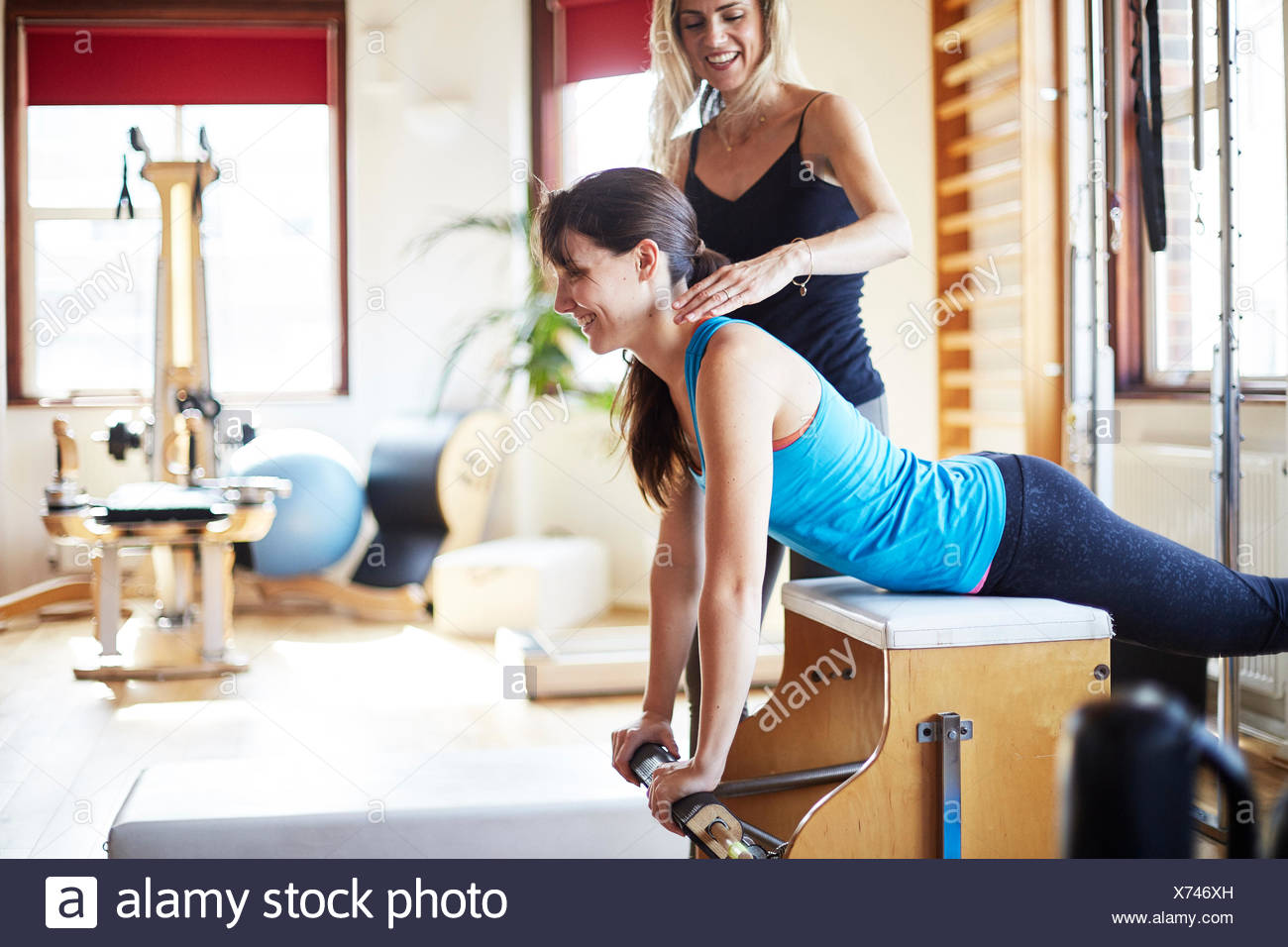 Young female student pushing up from combo chair in pilates gym Stock Photo