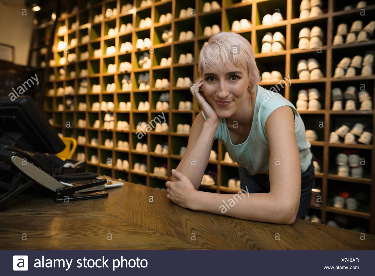 Portrait smiling worker leaning bowling shoes rental counter - Stock Image