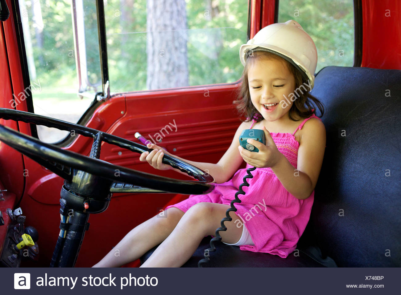 A young girl plays with a car's radio. - Stock Image