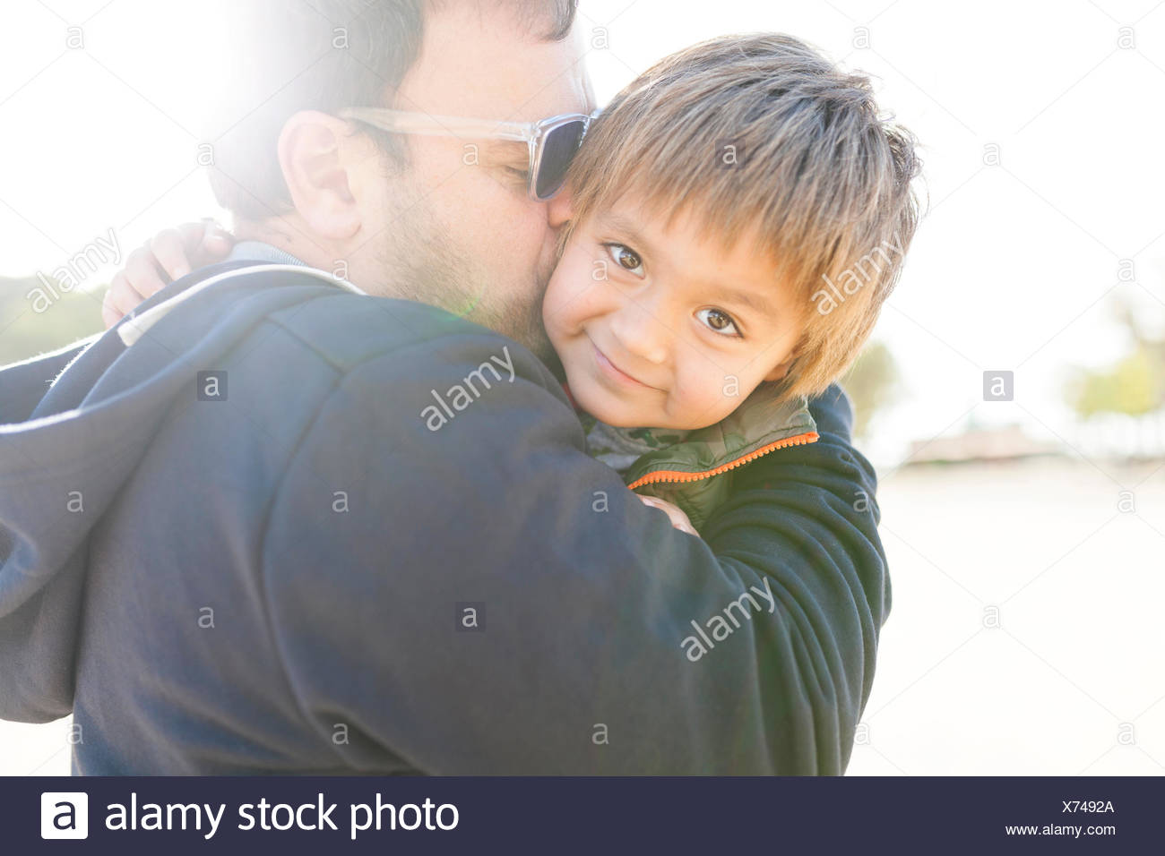 Portrait of smiling little boy hugging and kissing by his father - Stock Image
