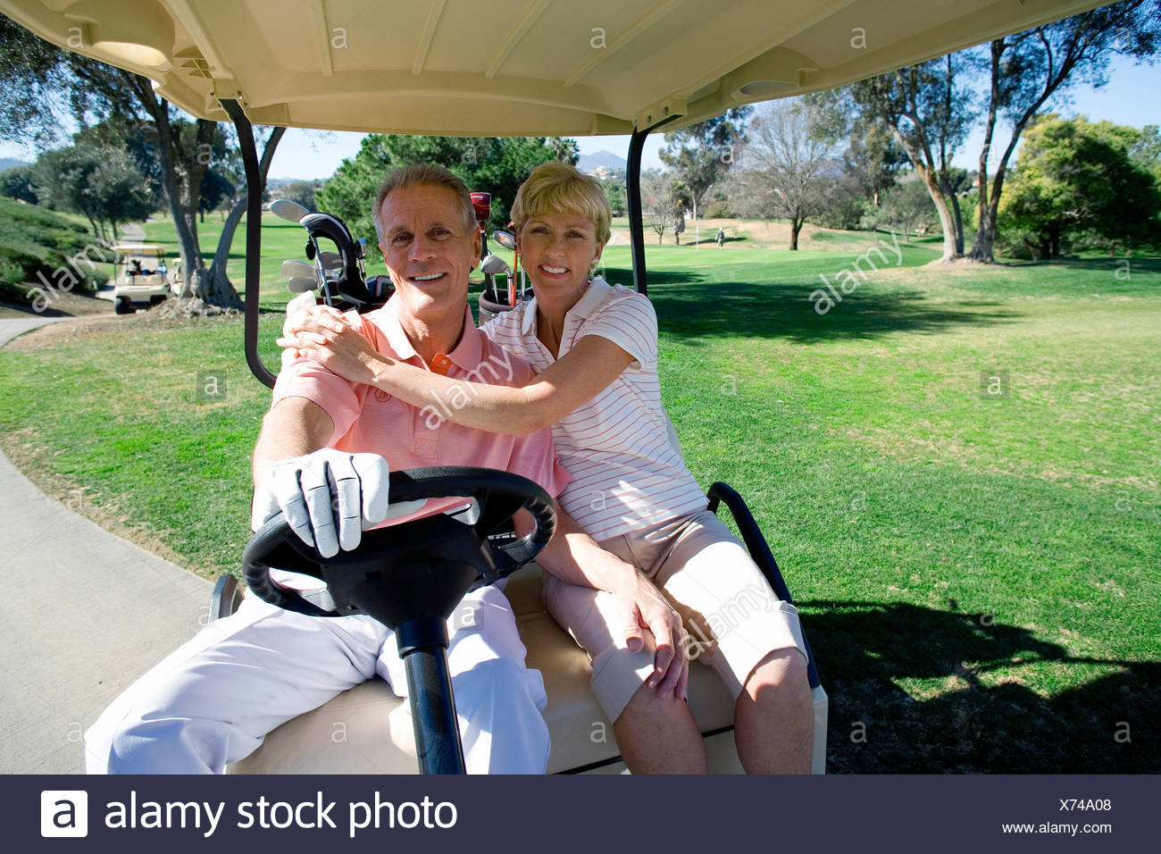 Mature couple sitting in golf buggy on golf course, man driving, woman embracing man, smiling, front view, portrait - Stock Image
