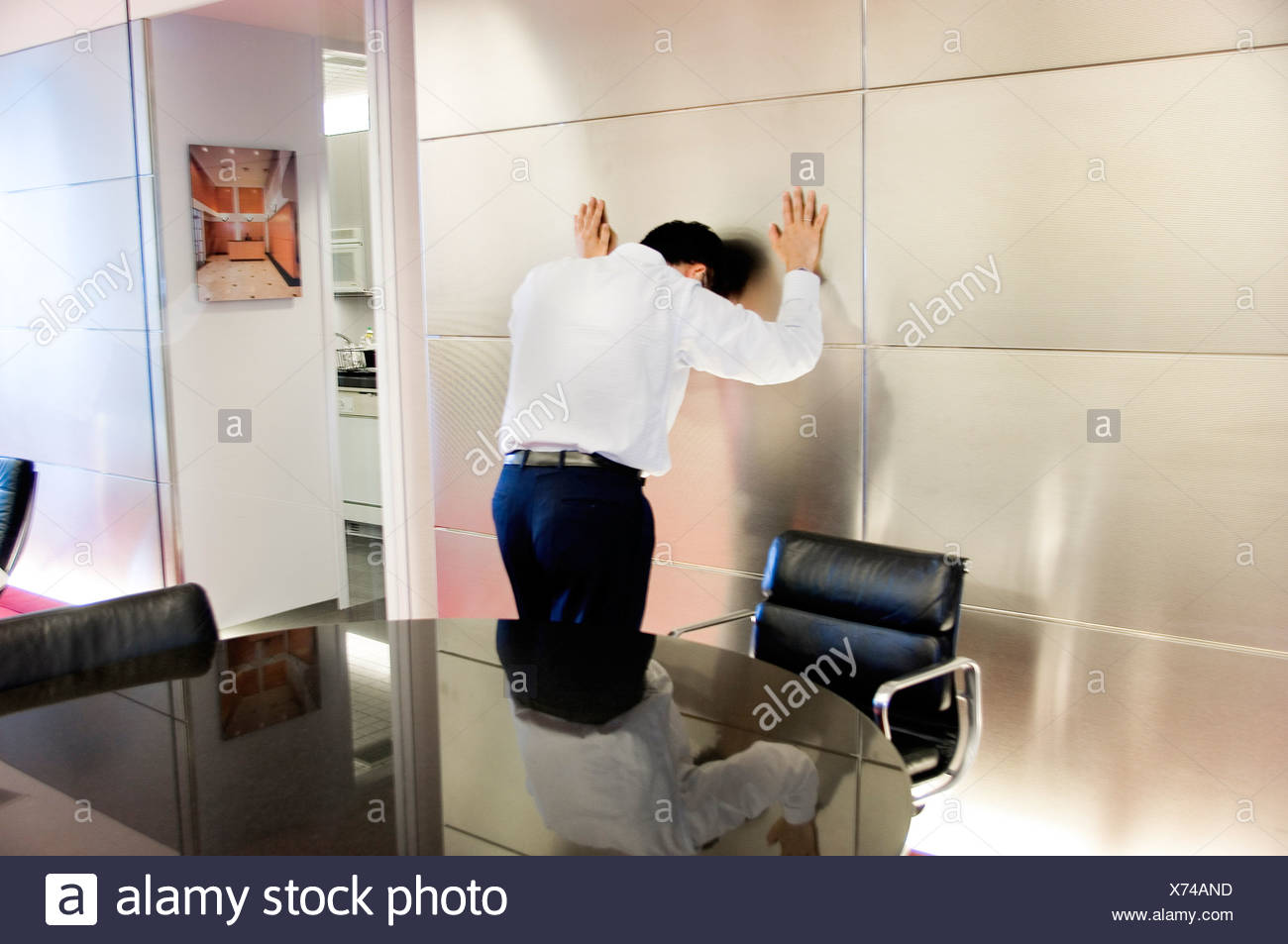 Businessman banging head against the wall - Stock Image