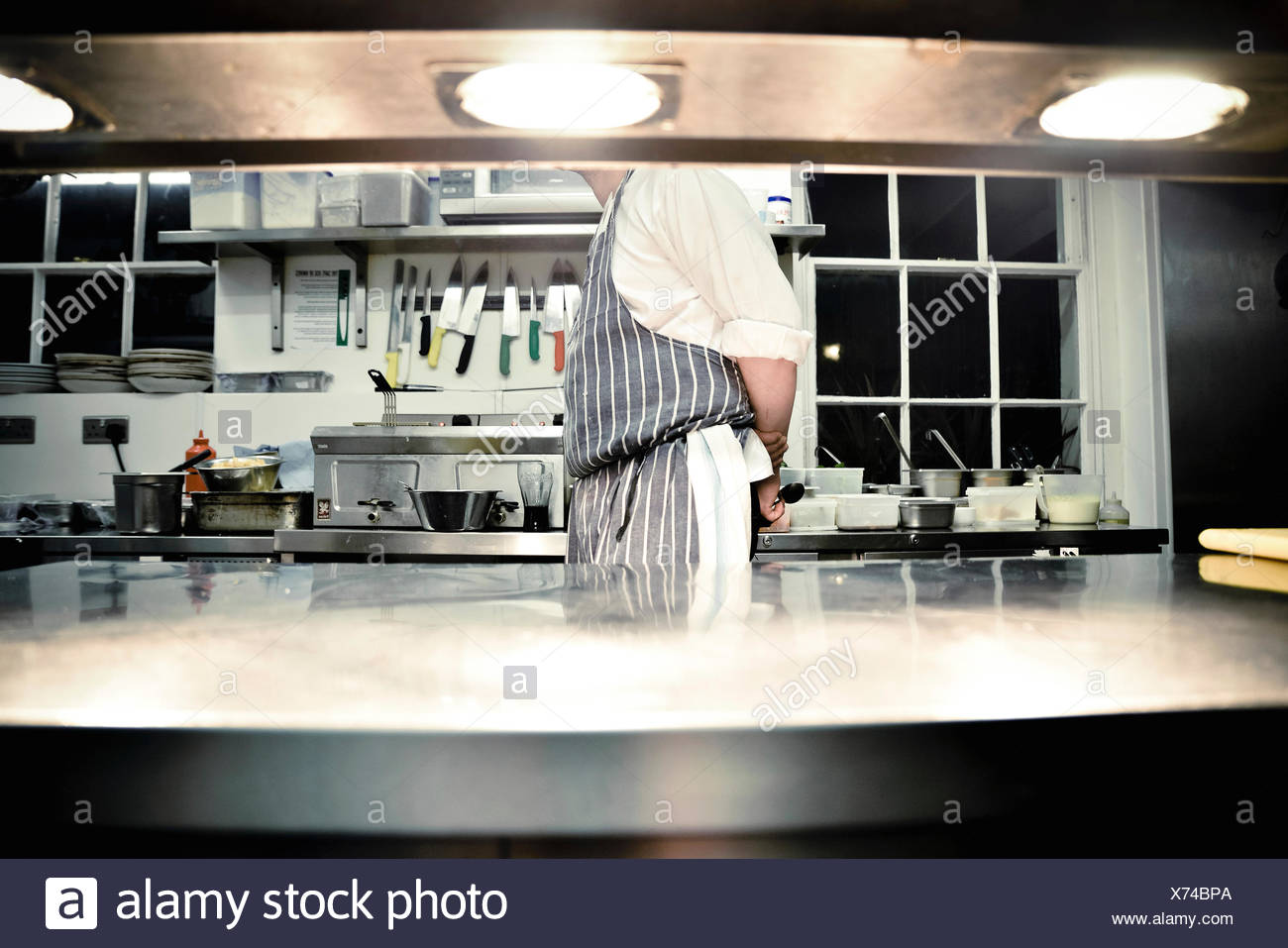 Chef standing in commercial kitchen - Stock Image