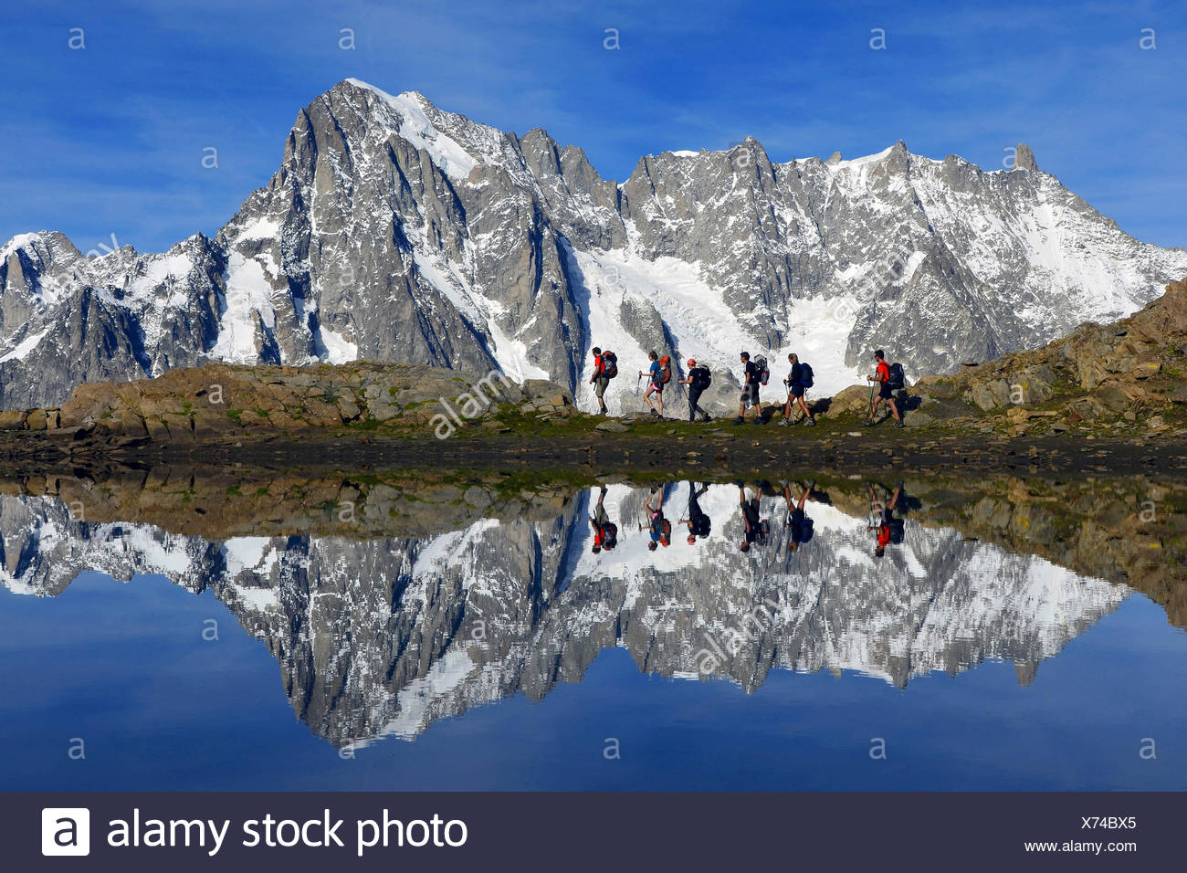 Trekkers and Mont Blanc (Monte Bianco) mirrored in the lake, route to pascal bivouac, Aosta Valley, Italy - Stock Image