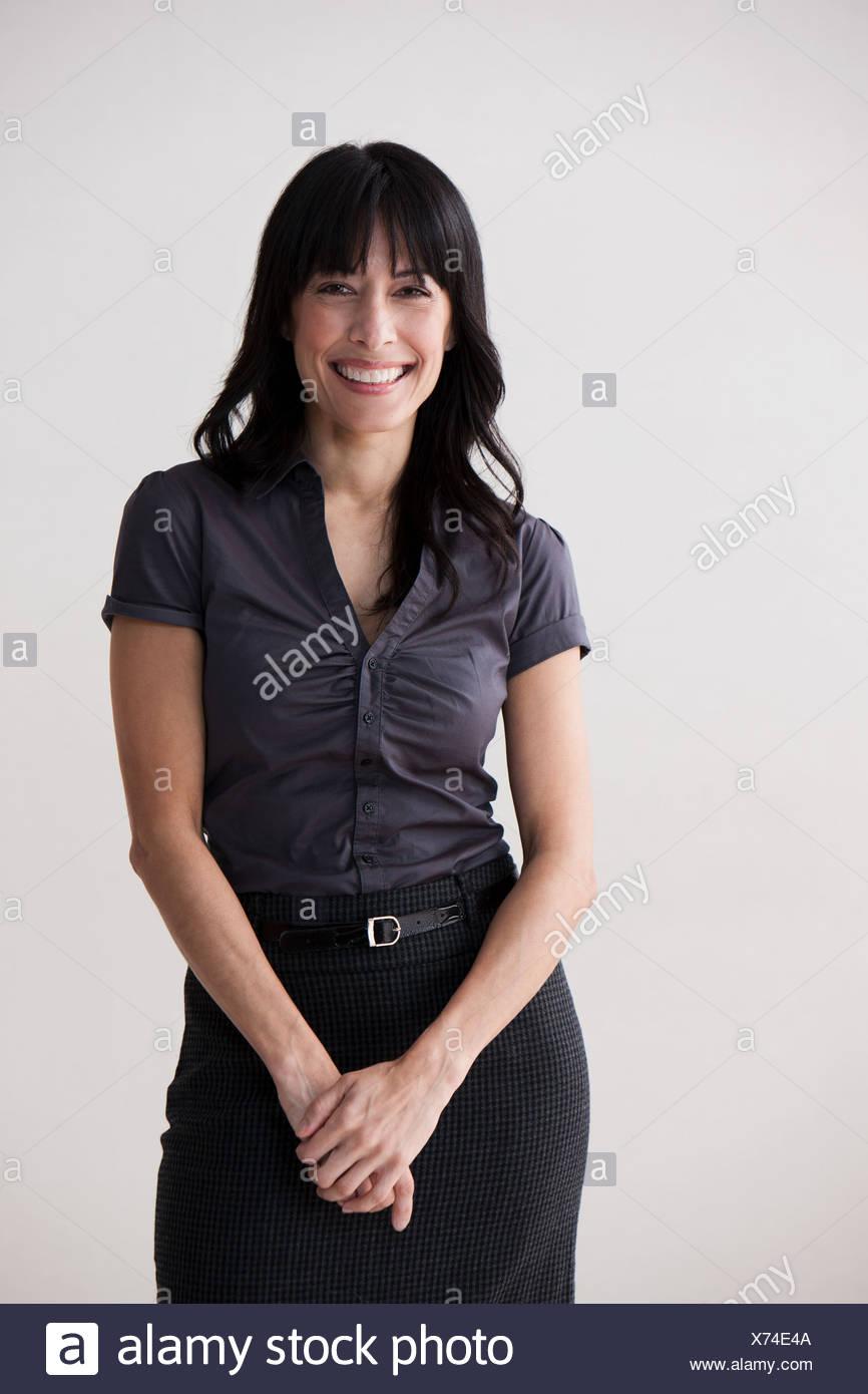 Portrait of mature woman smiling, studio shot - Stock Image