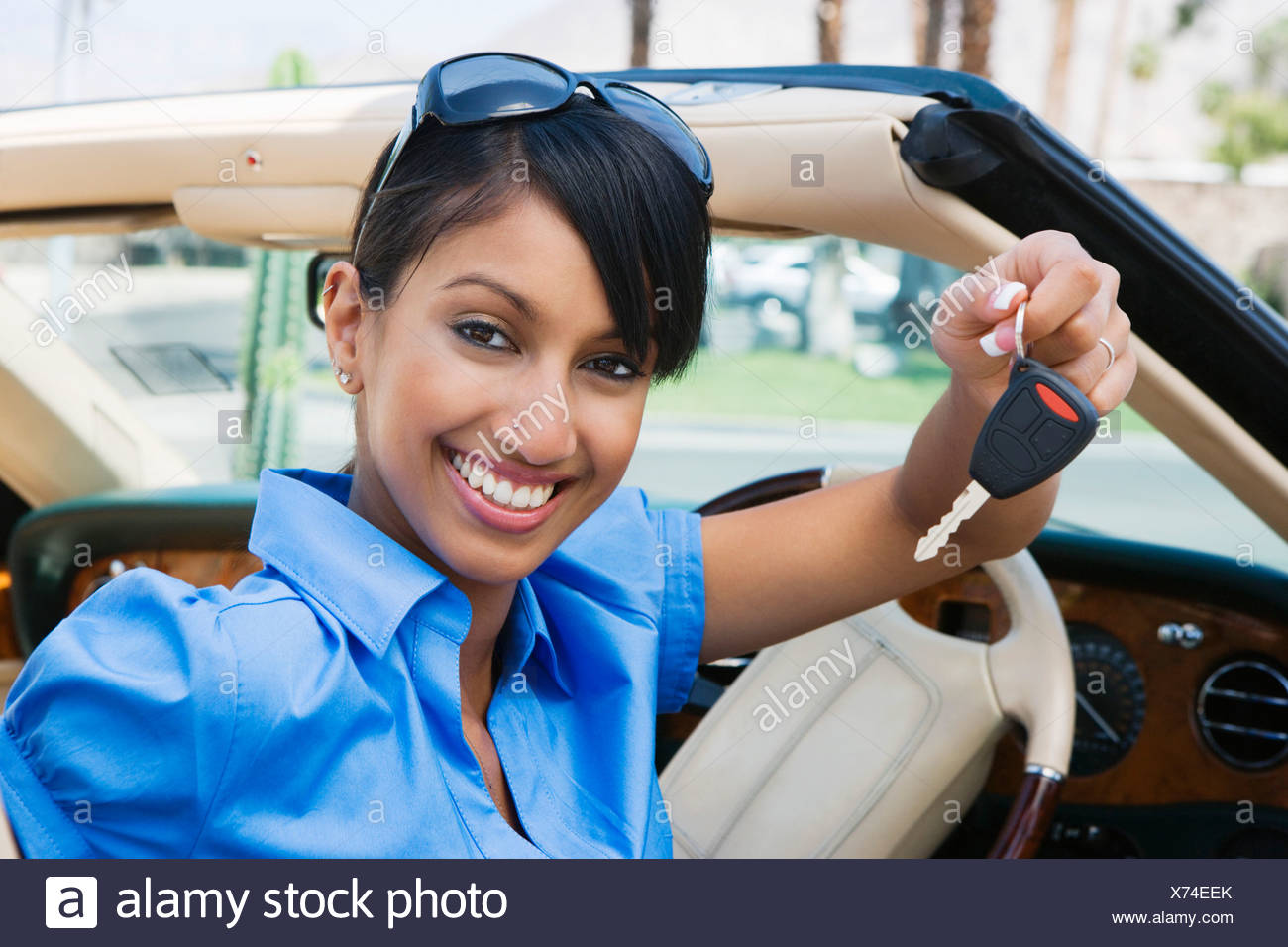 Young Woman Holding Key to Convertible - Stock Image