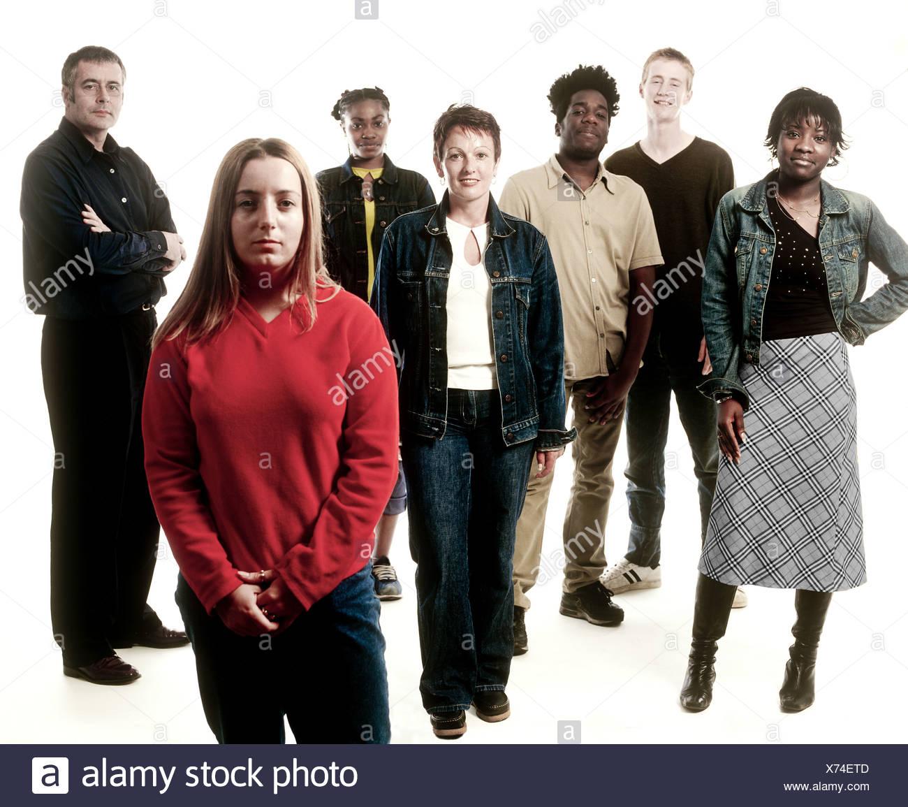 Group of seven people standing, studio shot - Stock Image