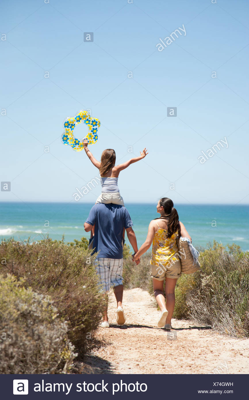 Family walking on beach path toward ocean - Stock Image