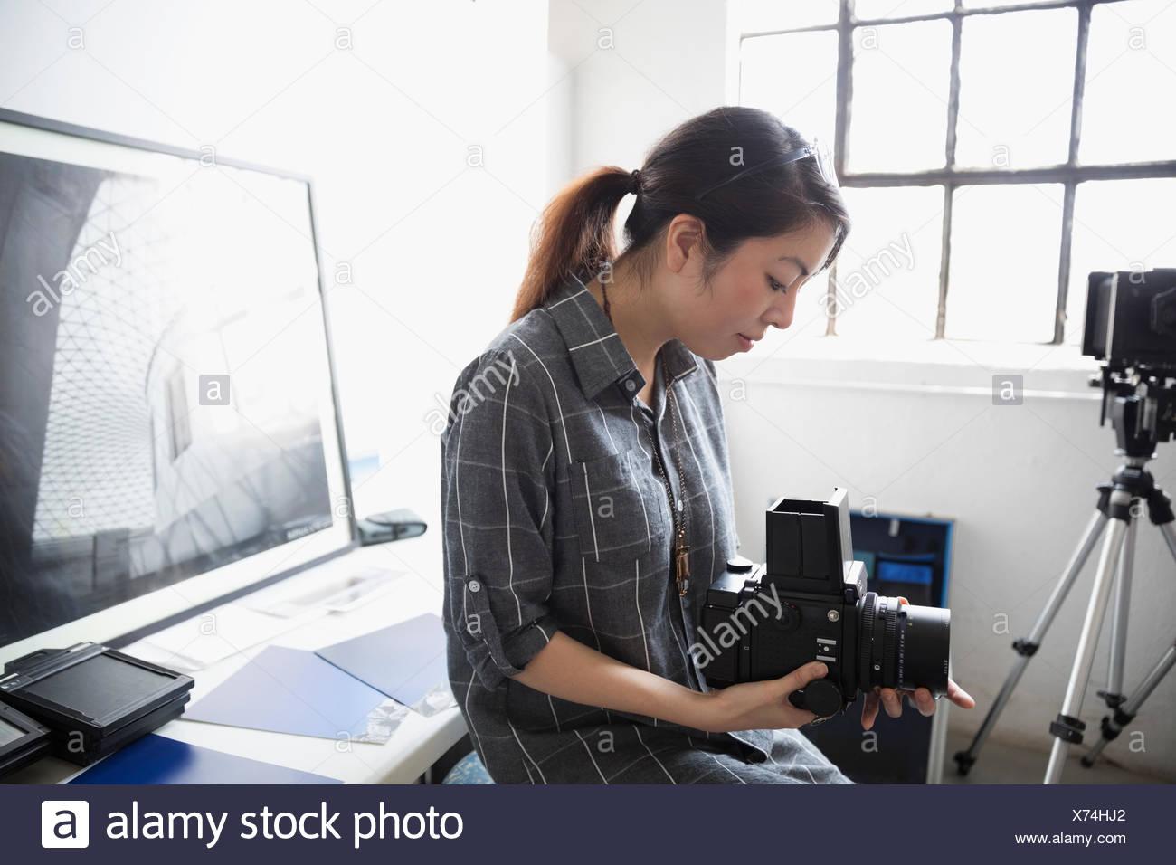 Female photographer adjusting digital camera lens in art studio - Stock Image