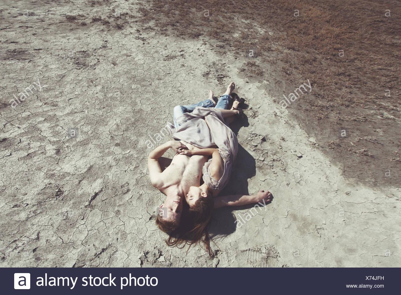 Couple lying on beach - Stock Image