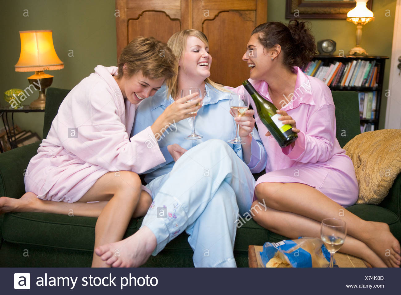 Three woman in night clothes sitting at home drinking wine - Stock Image