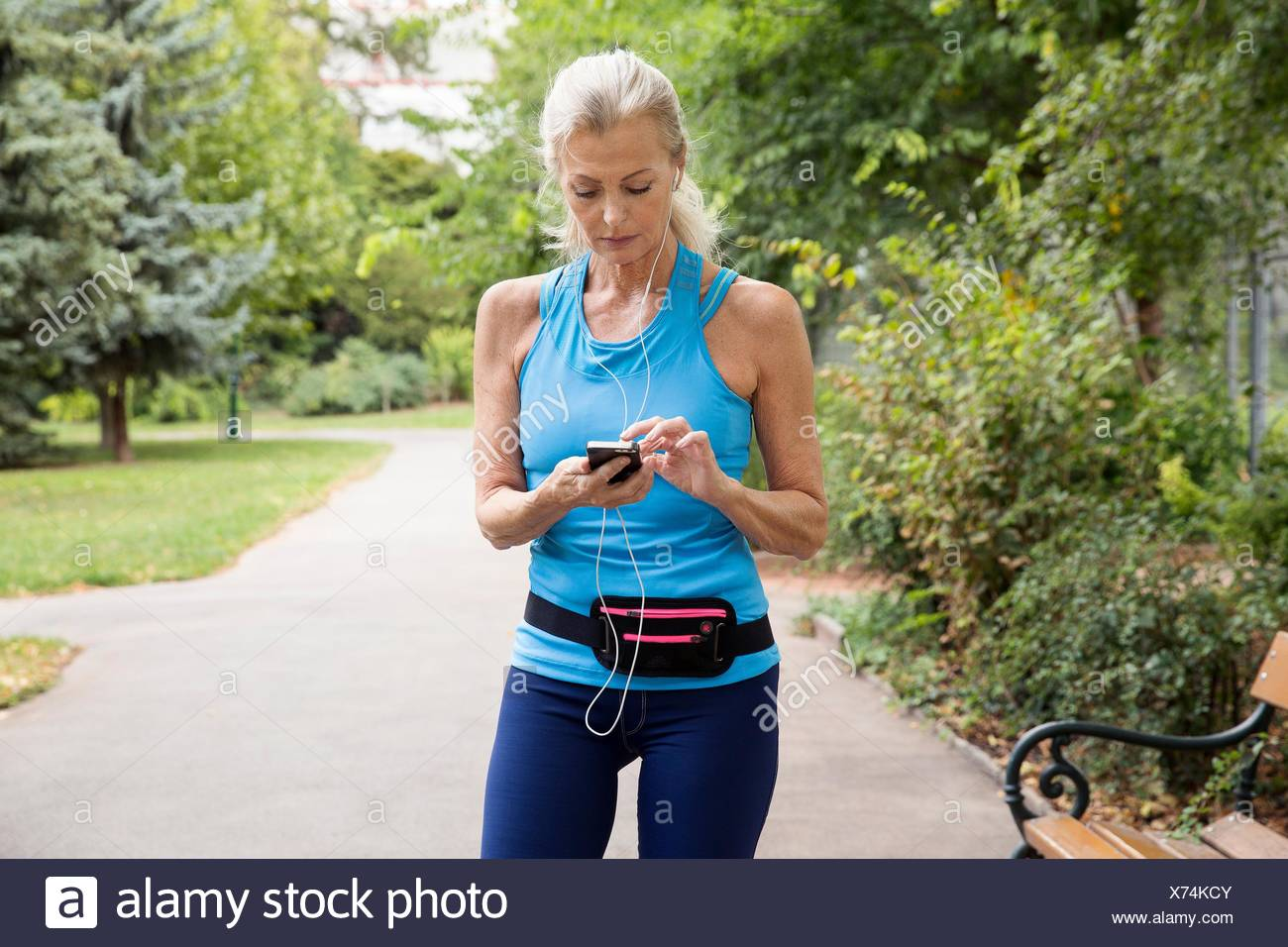 Mature woman choosing smartphone music whilst training in park - Stock Image
