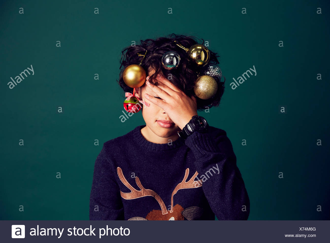 ef7f8e845f3 Teenage boy wearing Christmas jumper, and baubles in hair, covering ...