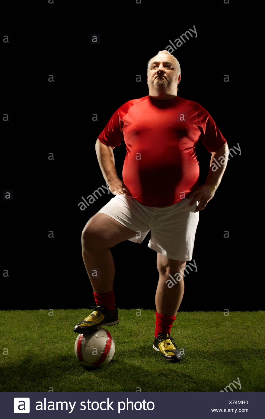 Large sportsman with foot on football - Stock Image