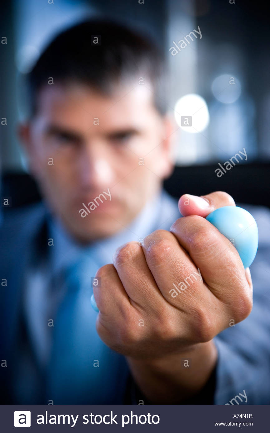 Close up of a businessman's hand squeezing a stress toy - Stock Image