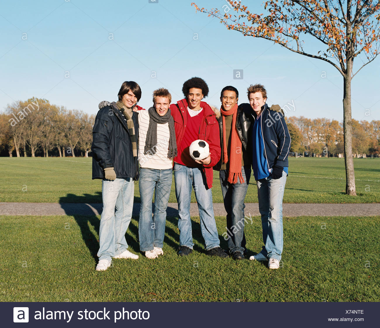 Men with a football in park - Stock Image